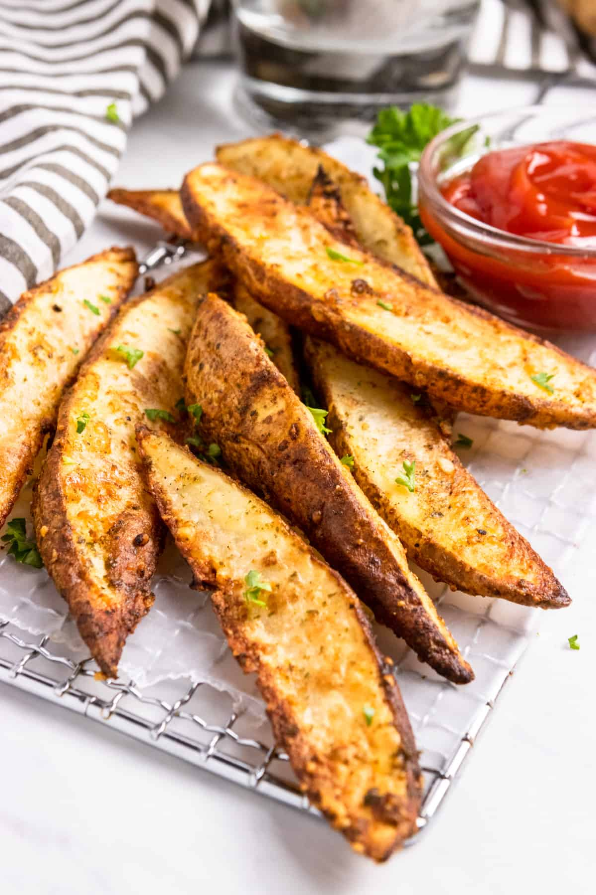 air fryer potato wedges on wax paper with ketchup.