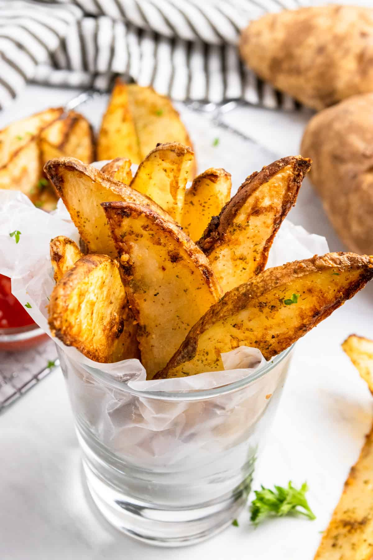 Crispy air fried potato wedges in glass with ketchup.