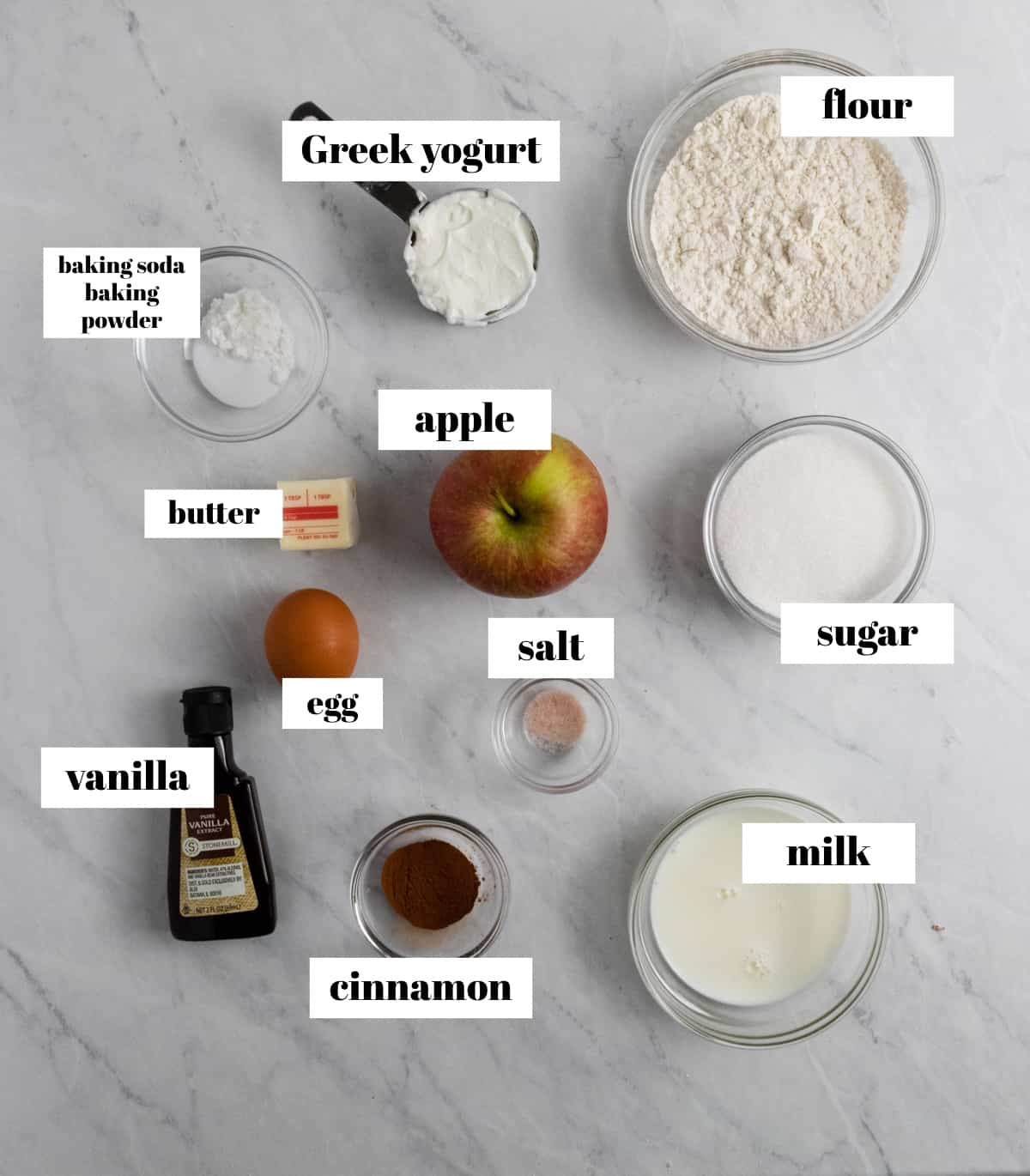 Flour, apple, sugar, cinnamon and other ingredients labeled on counter.
