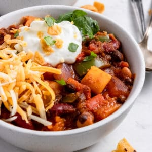 Butternut Squash Chili in bowl with sour cream, cheese and cilantro.