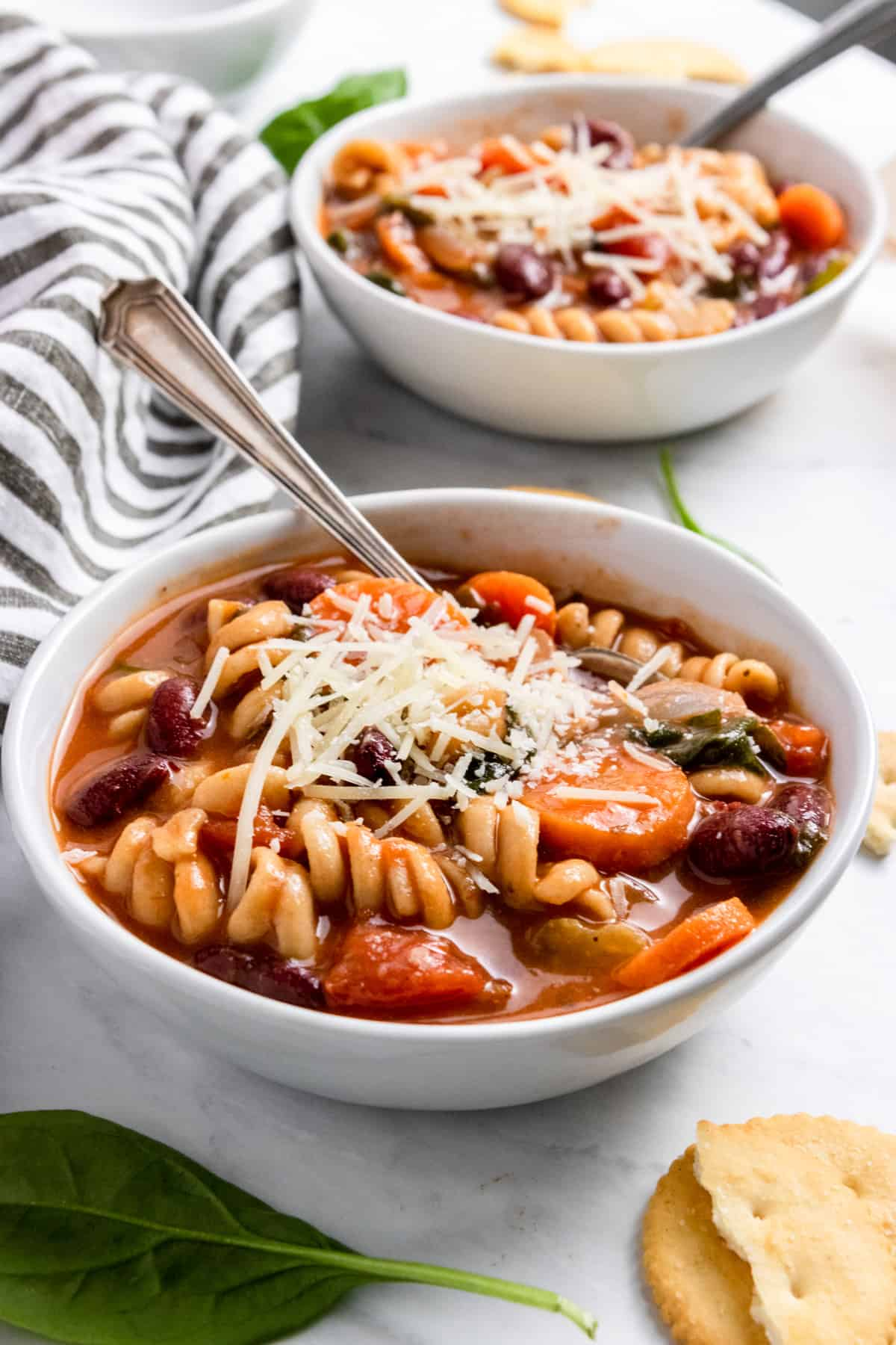 Chunky vegetable soup in bowl with spoon and cheese.