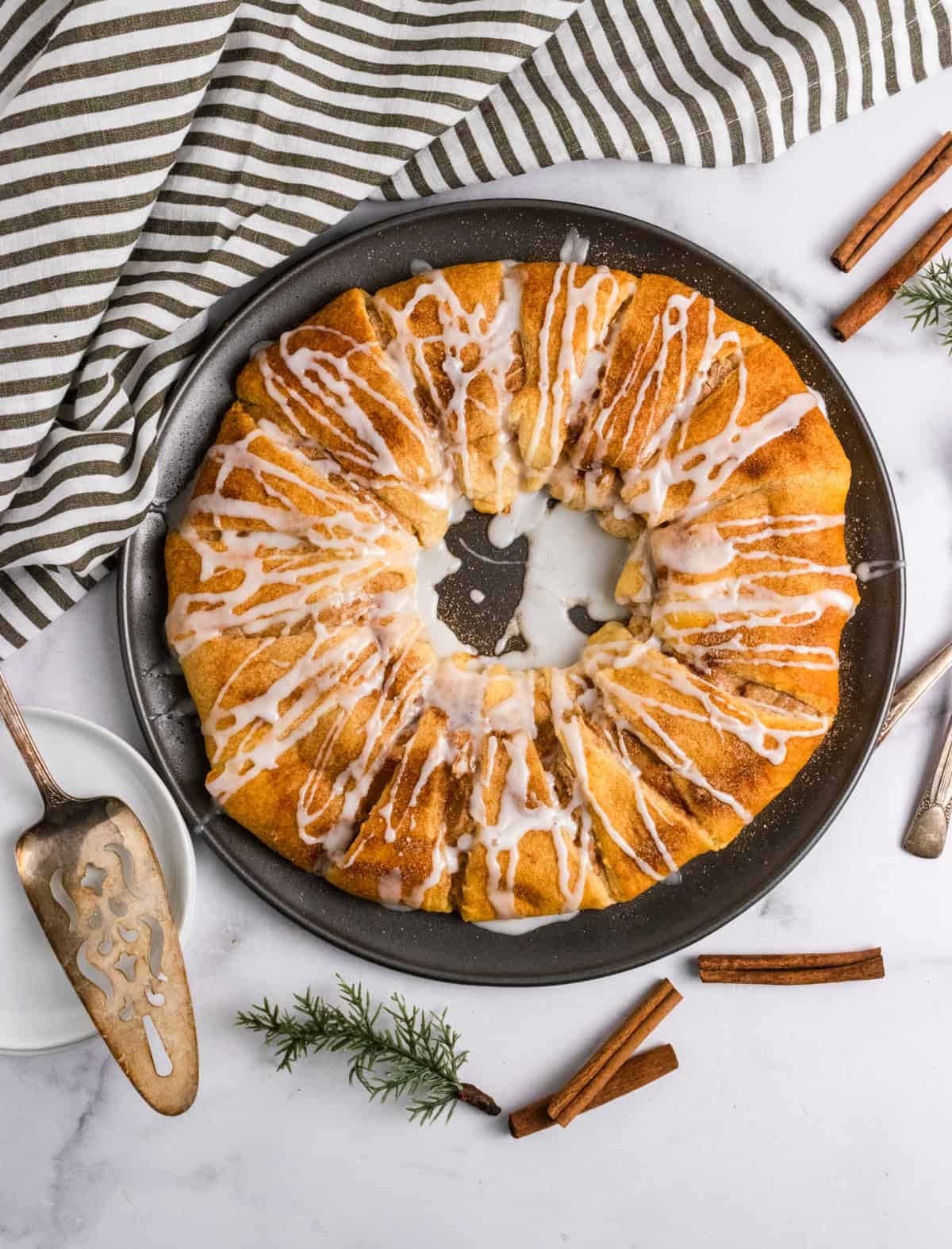 Crescent roll wreath with cinnamon and icing on pan.