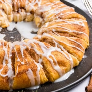 Cinnamon Cheesecake stuffed crescent wreath on pan with icing.