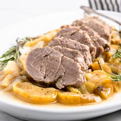 Sliced Instant Pot Pork Tenderloin on plate with apples.