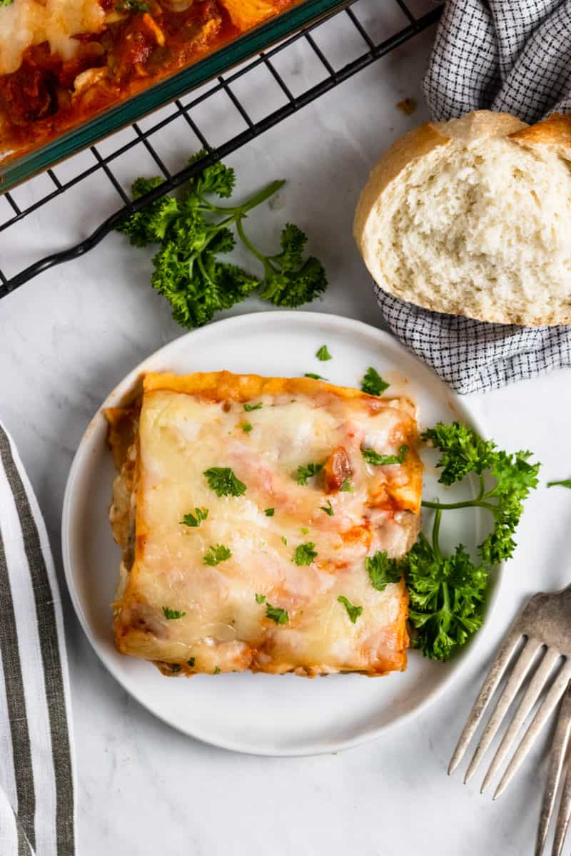 Overhead of lasagna on plate with bread.
