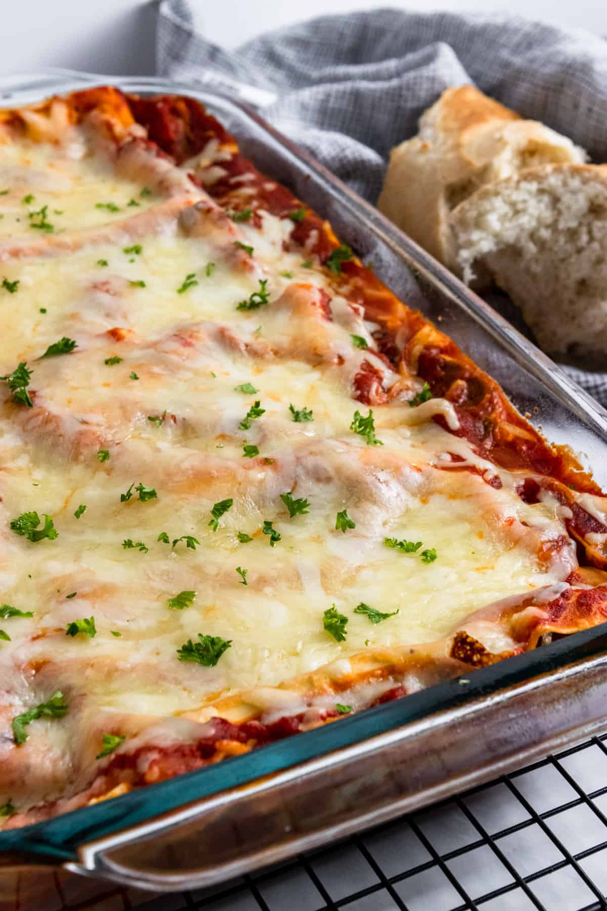 Pan with lasagna and bread beside it.