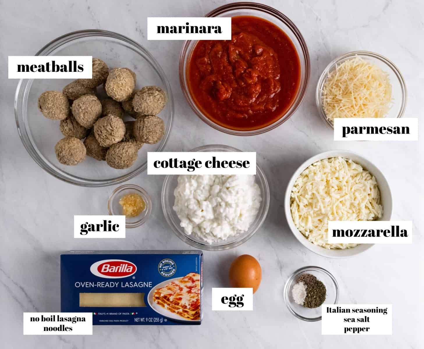 Lasagna ingredients labeled on counter including cheese, noodles, meatballs and more.