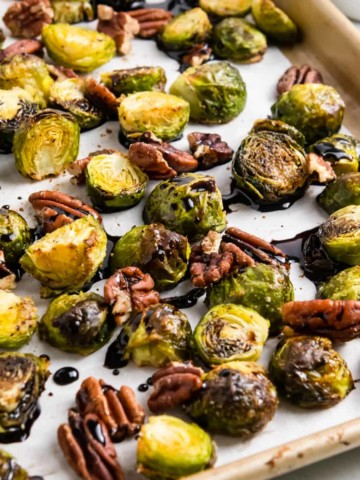 Brussels sprouts with pecans and glaze on pan.