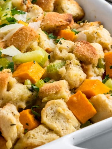 Butternut squash stuffing in white dish with parsley.