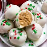 Christmas Oreo balls with Golden oreos and white coating with red and green holiday sprinkles.