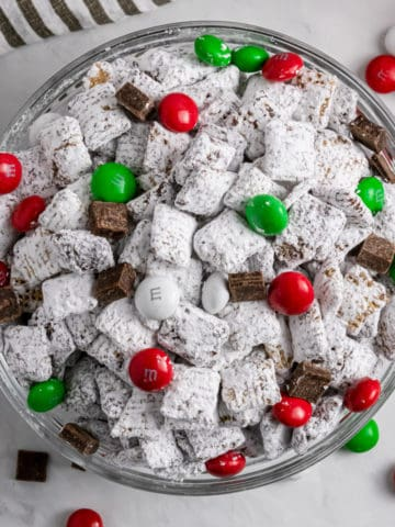Christmas Puppy Chow in bowl with red and green candies.