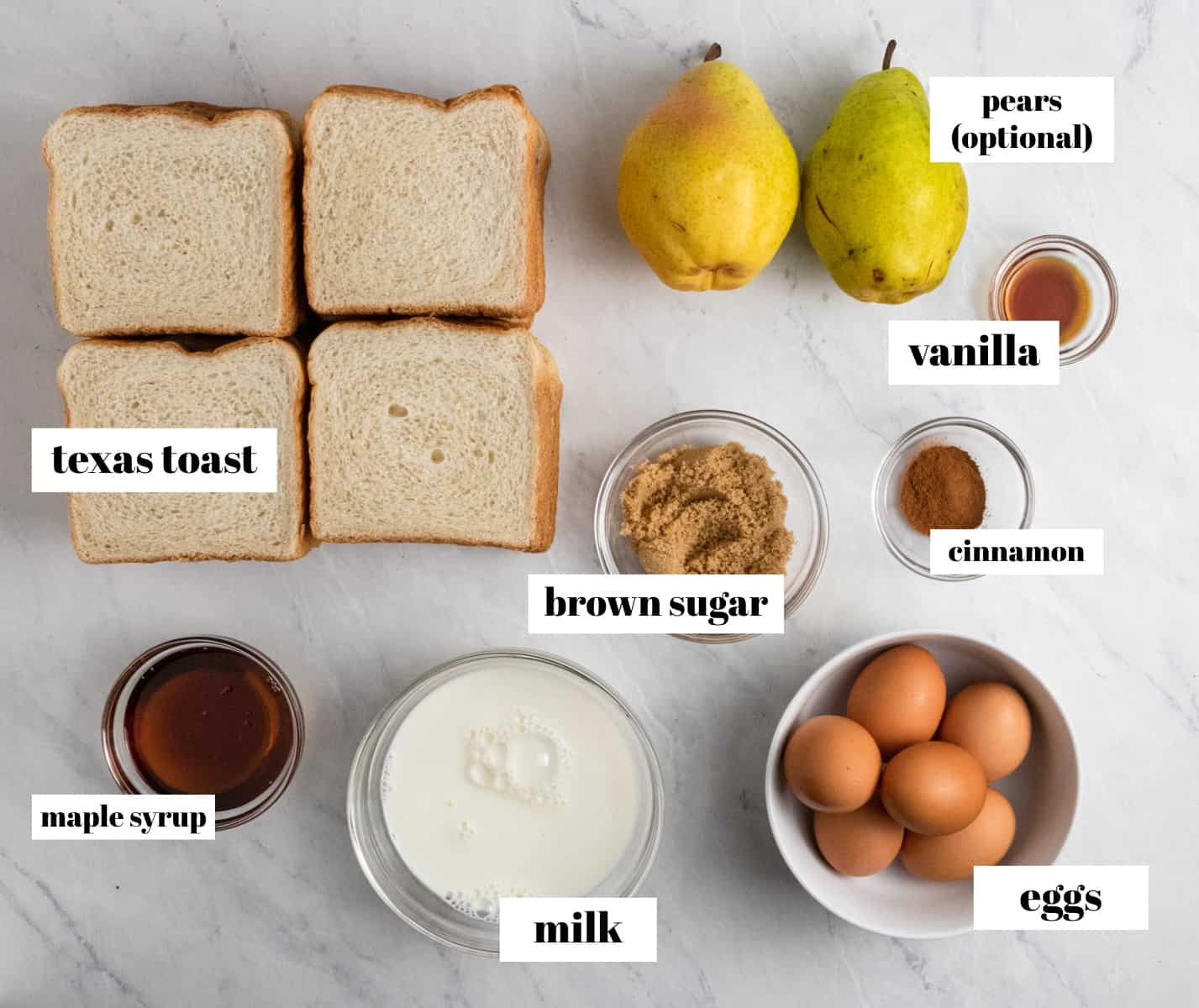 Bread, eggs, milk, syrup and other ingredients labeled on a counter.