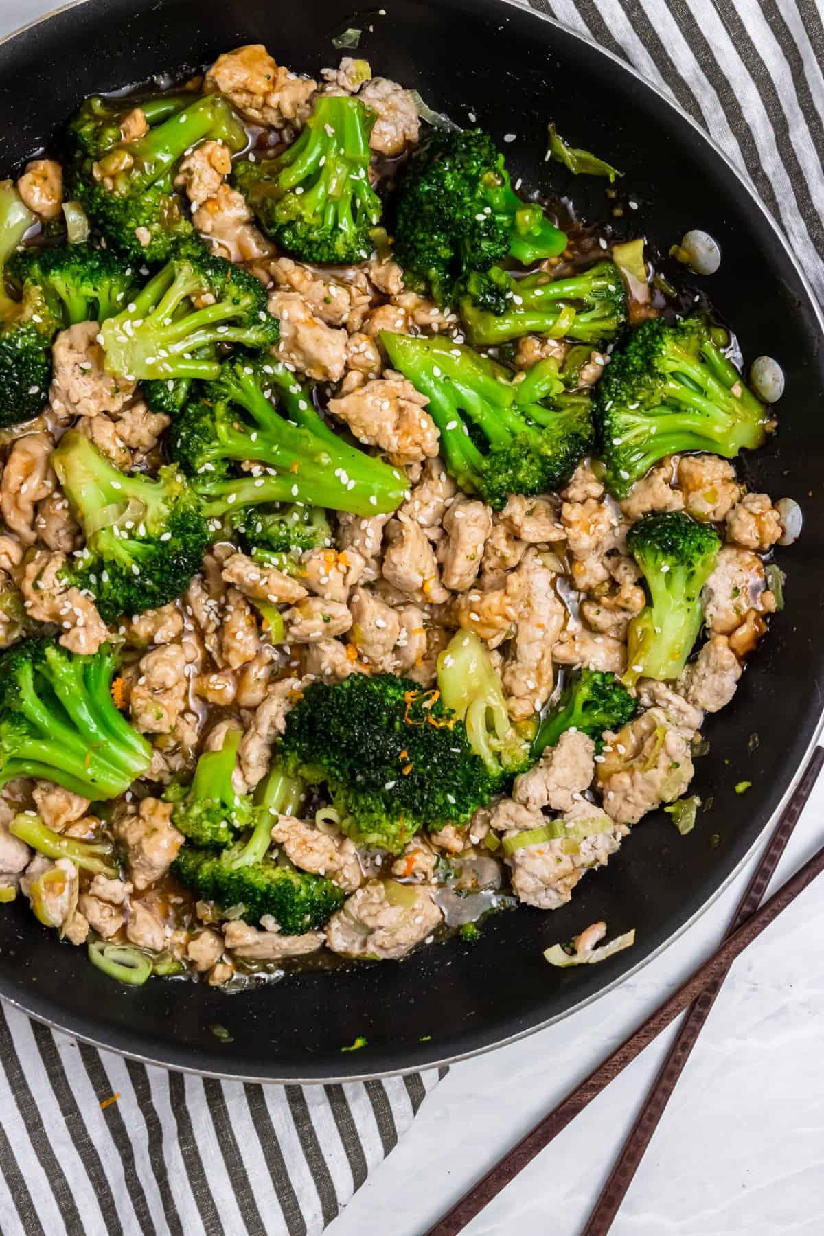 Ground turkey teriyaki in skillet with broccoli and chopsticks.