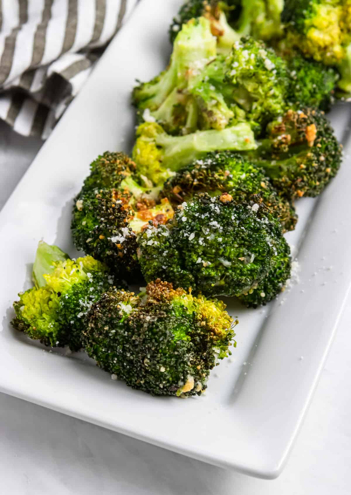 Plate of air fried broccoli with parmesan.