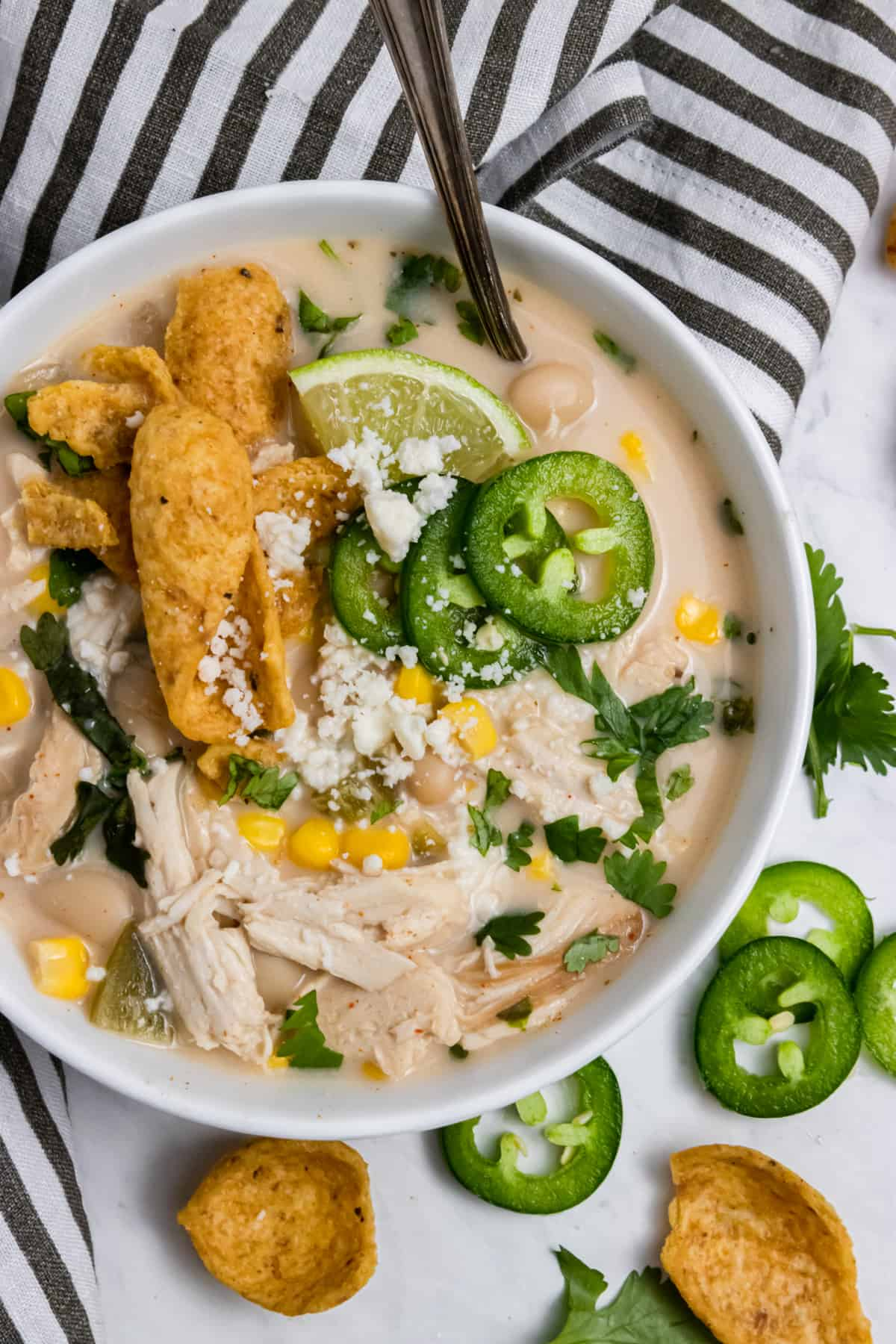 White chicken chili in white bowl with cheese, corn, chips and more.