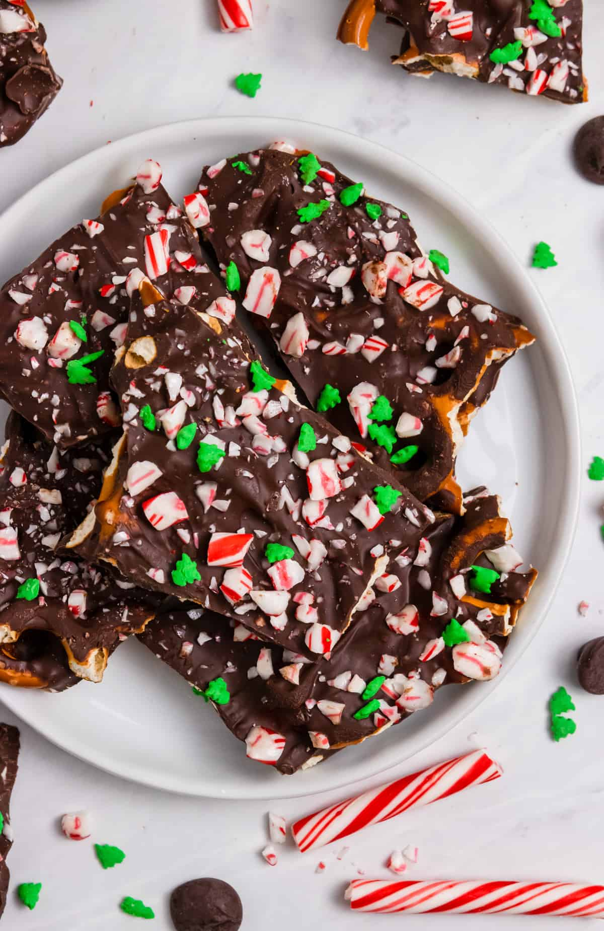 Pretzel bark with candy canes and green sprinkles on plate.