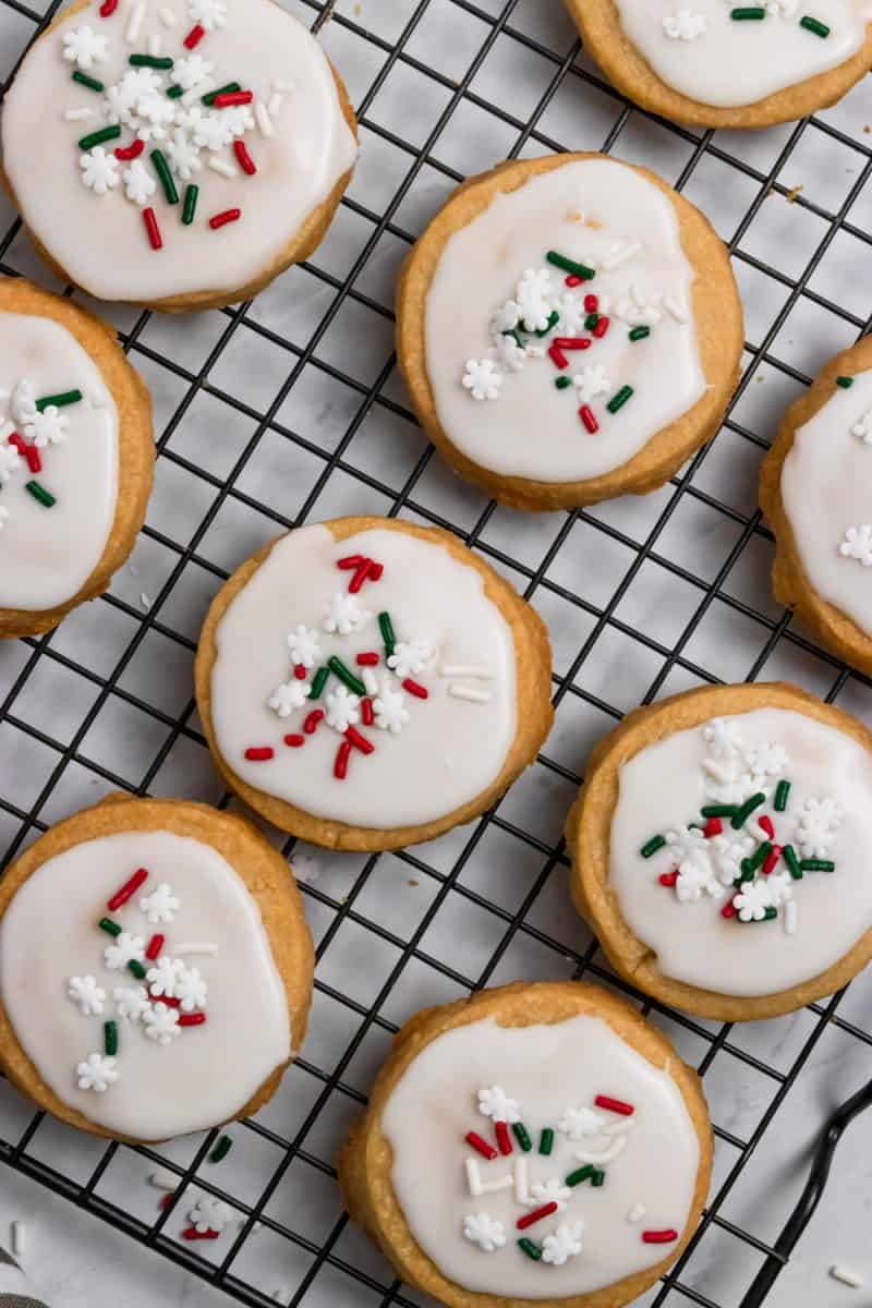 Christmas shortbread cookies iced on cooling rack.
