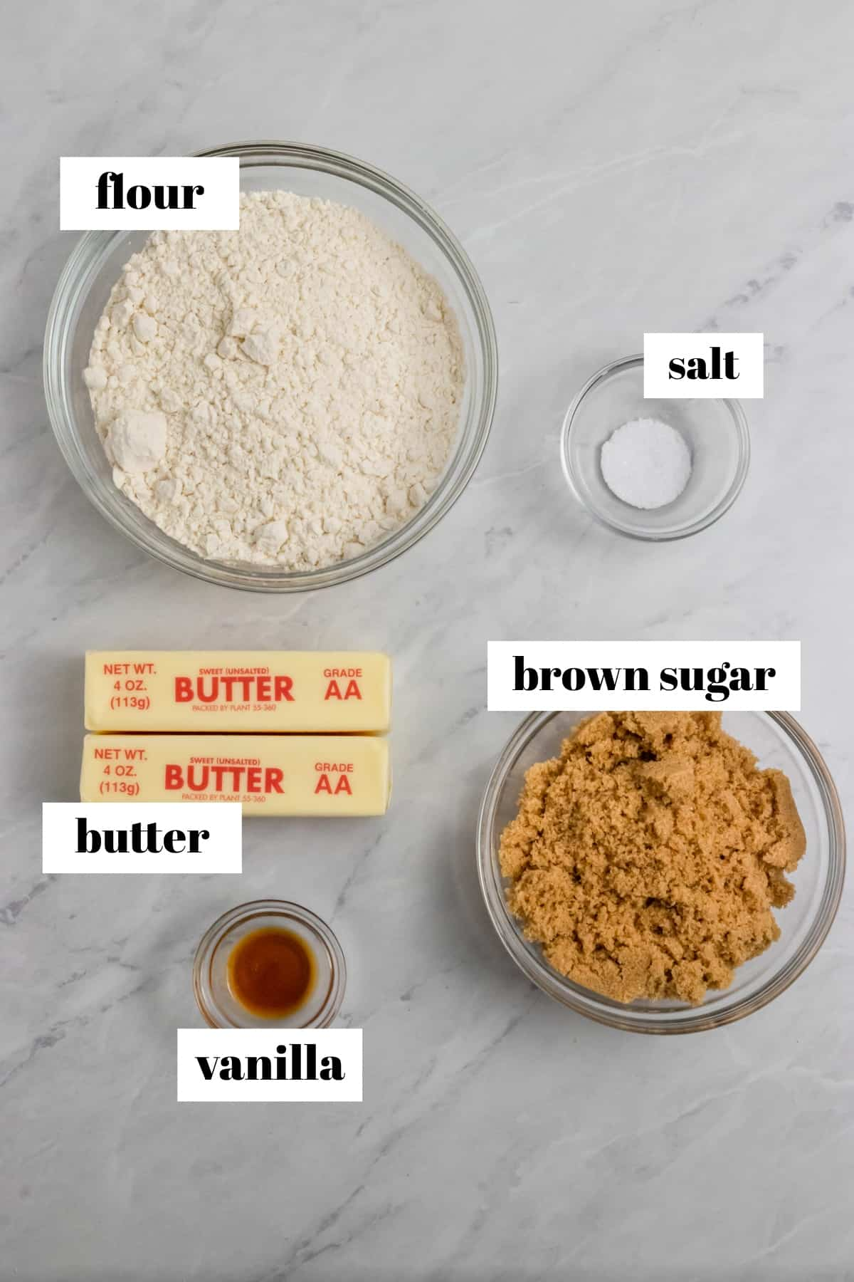 Butter, flour, brown sugar and vanilla labeled on counter.