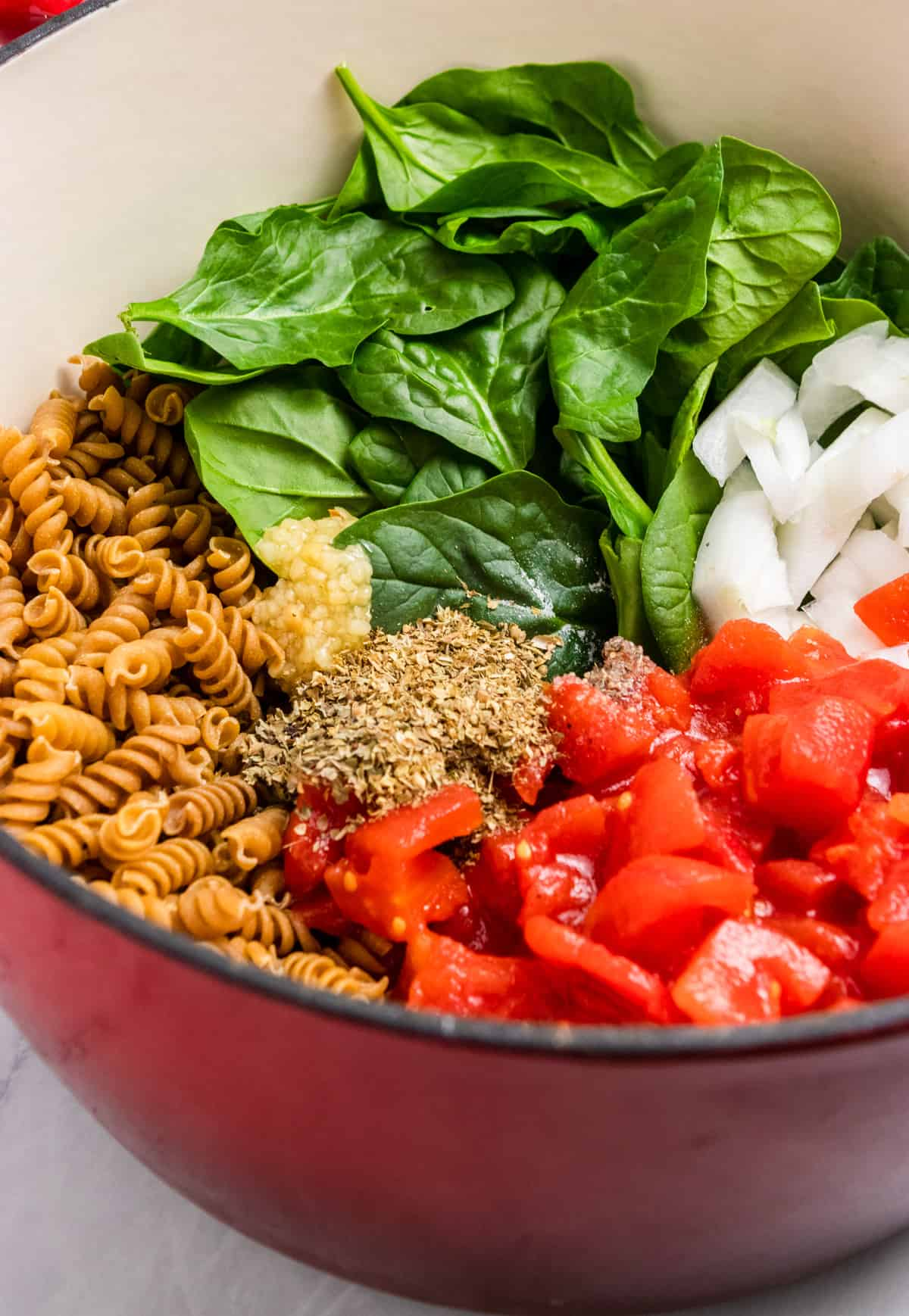 Tomatoes, spinach, rotini and ingredients in pot.