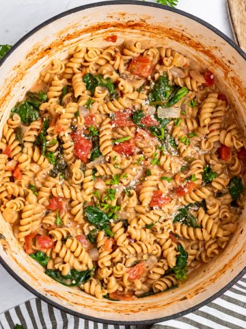 One pot pasta in pan with spinach and parsley.