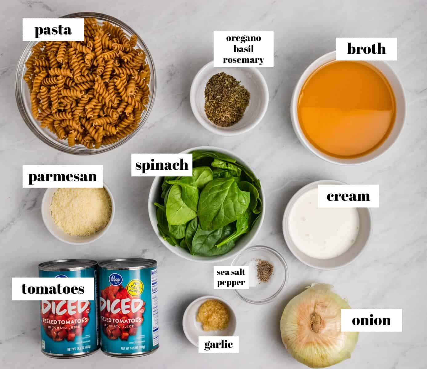 Rotini, broth, spinach, cheese and other ingredients on counter labeled.