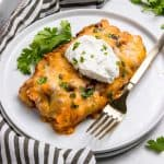 Ground turkey enchilada on white plate with sour cream and cilantro.
