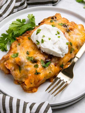 Ground turkey enchilada on white plate with sour cream and cilantro.