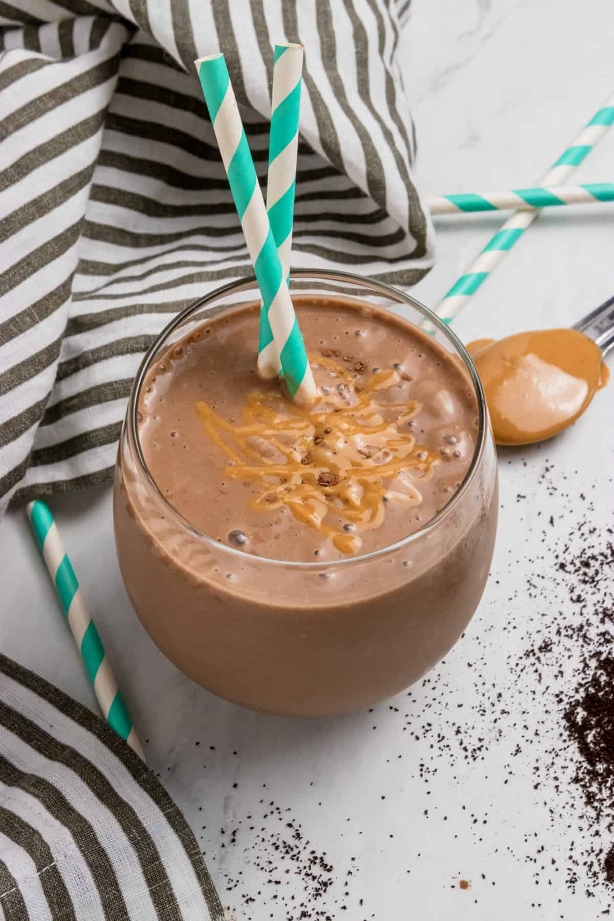 Peanut butter coffee smoothie in glass with straws.