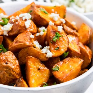 Potatoes in white bowl with buffalo sauce.