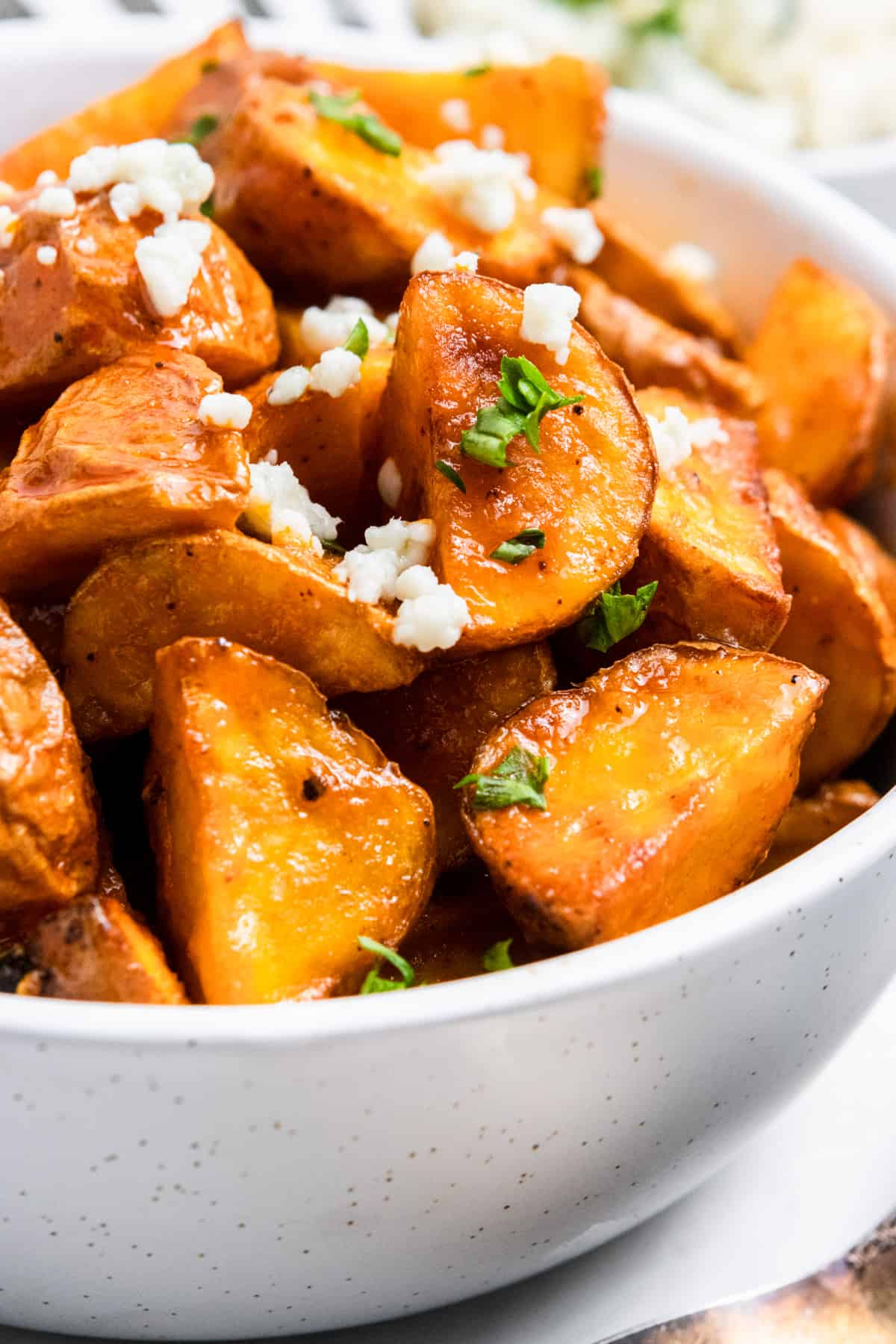 Air fryer mini buffalo potatoes in bowl with parsley and blue cheese.