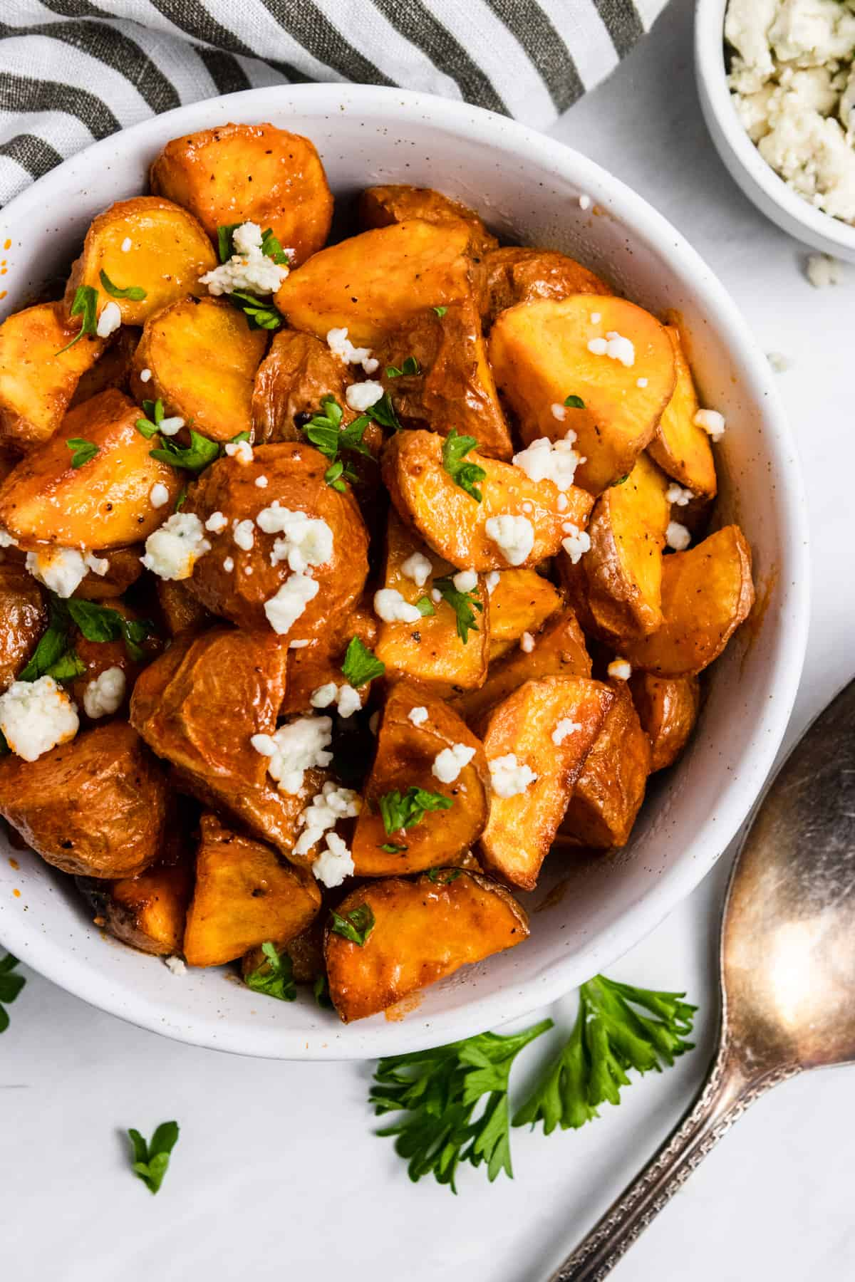 Diced potatoes in bowl with buffalo sauce.
