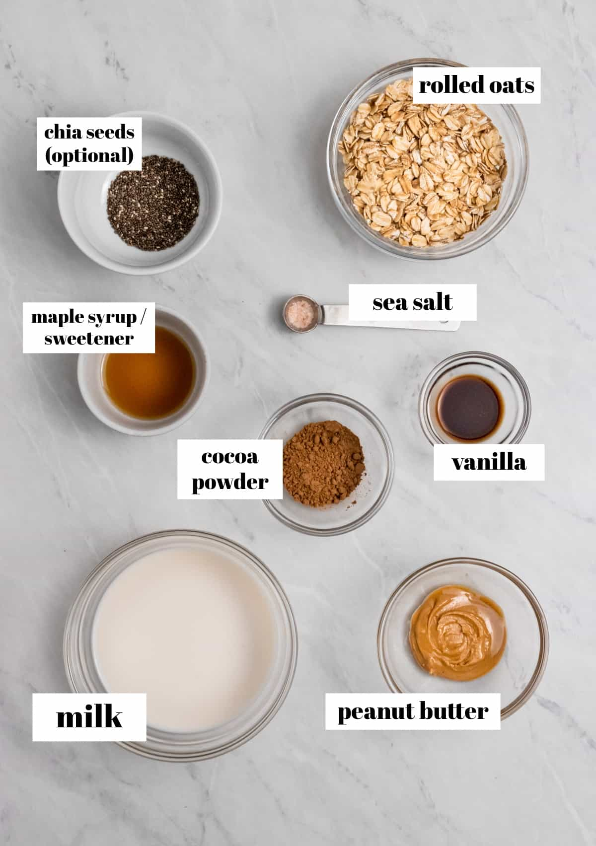 Rolled oats, cocoa powder, maple, and other ingredients in bowls on counter.