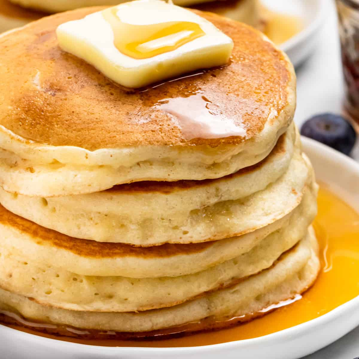 Stack of fluffy pancakes with butter and syrup drizzle.