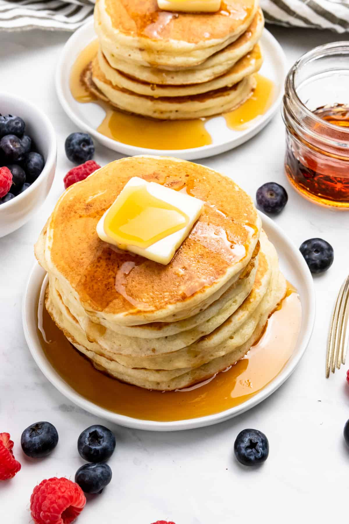 Stack of pancakes with butter, berries and syrup.