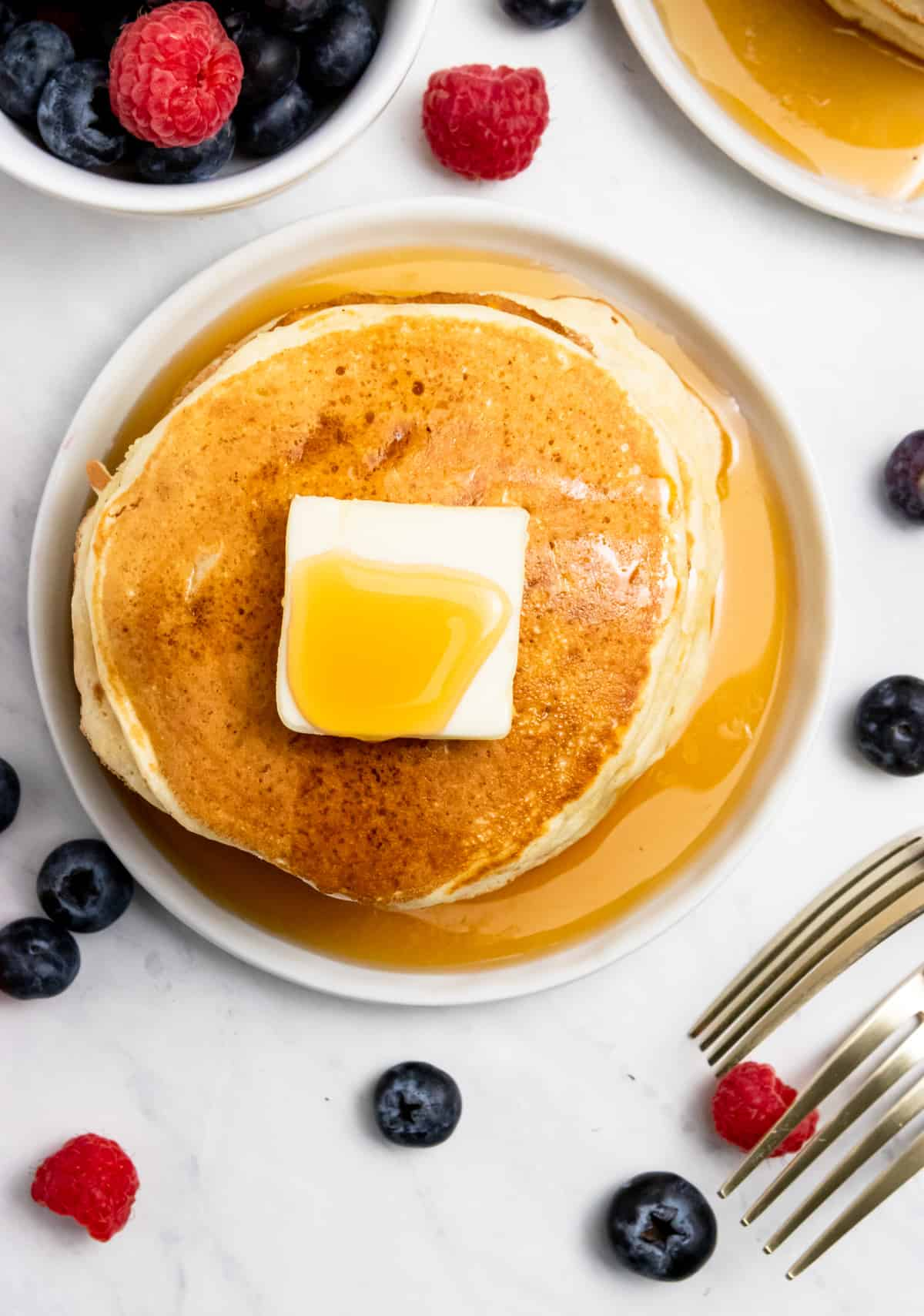 Overhead view of fluffy pancakes with butter and berries.