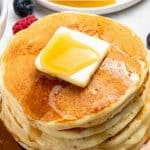 Stack of fluffy pancakes with butter and syrup.