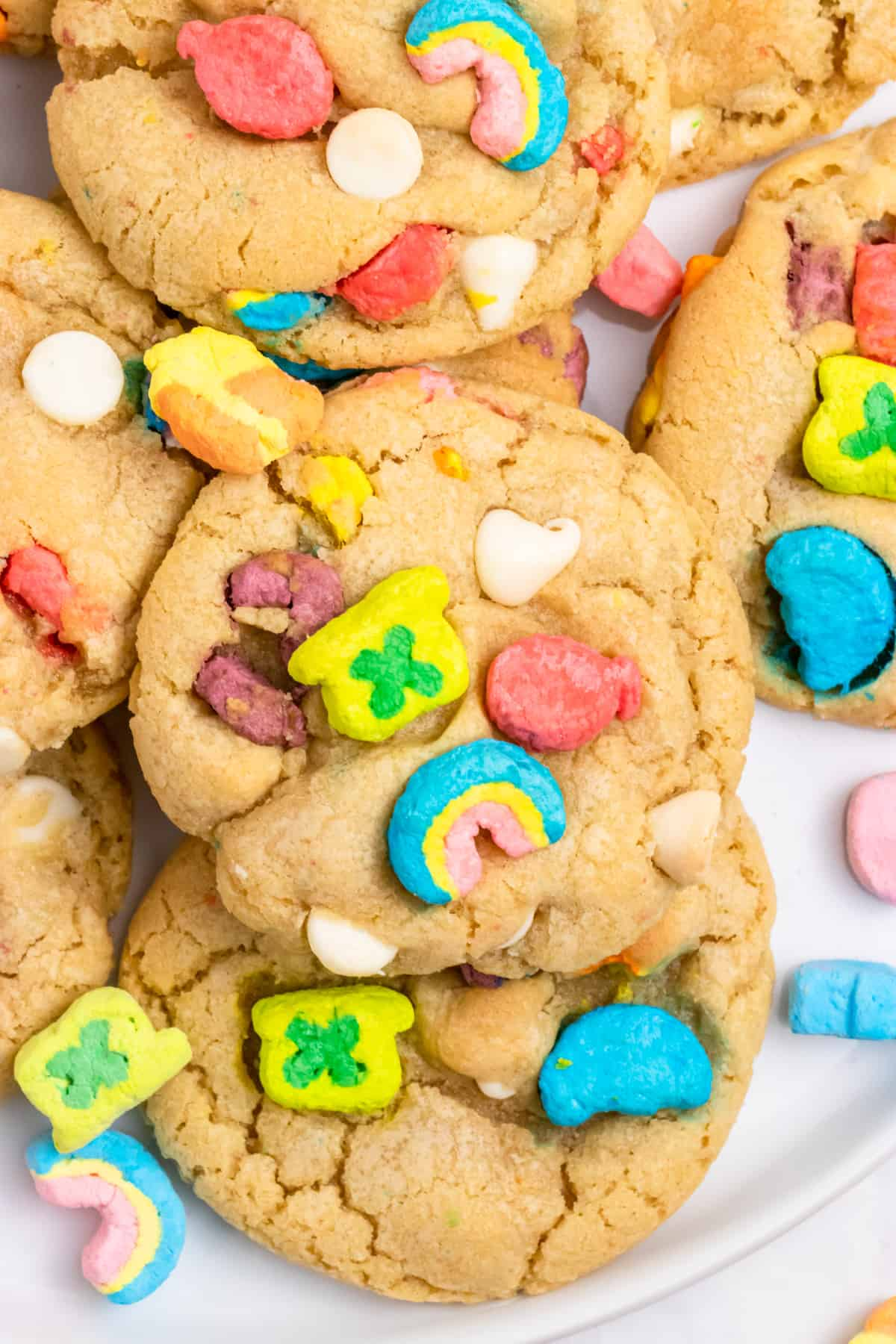 Cookies with lucky charm marshmallows and white chocolate chips on plate.