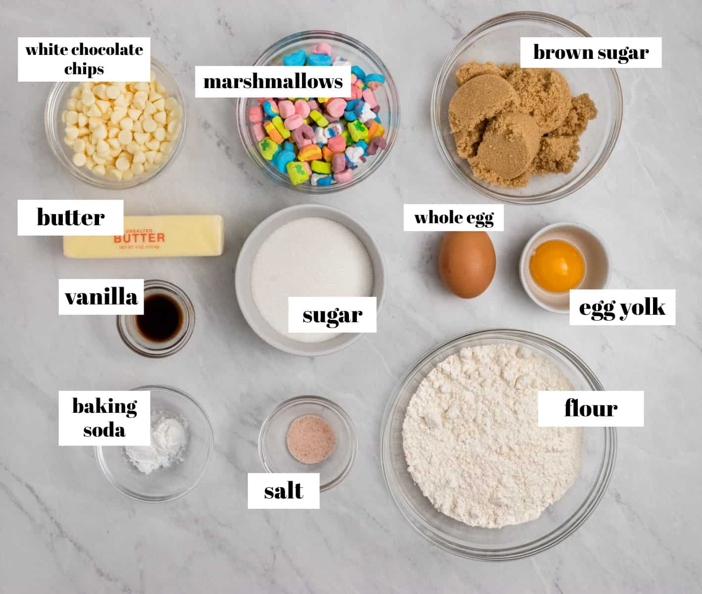 Flour, white chocolate chips, egg yolk, and ingredients labeled on counter.