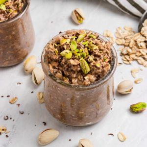 Pistachio oatmeal with chocolate in jar.