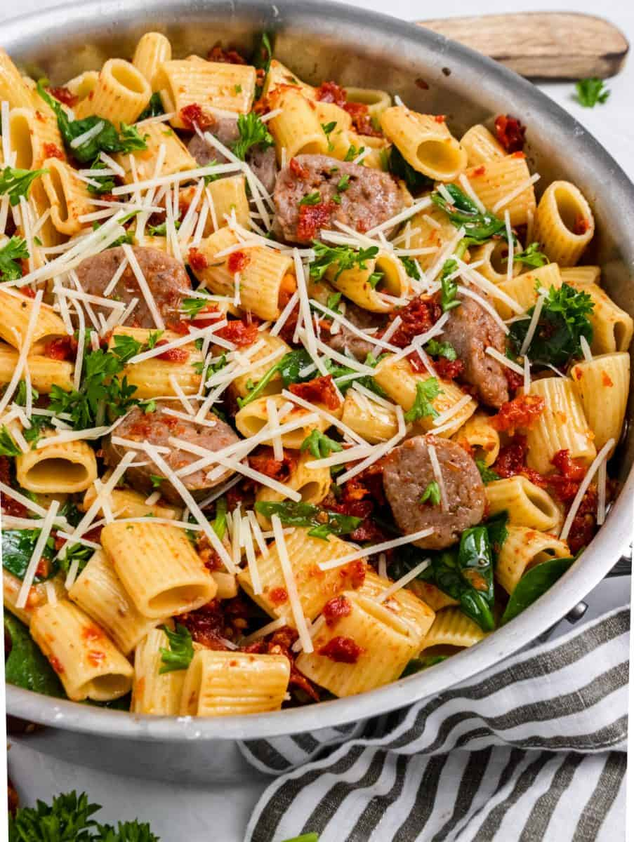 Sun dried tomato pasta in skillet with sausages, spinach and parmesan cheese.