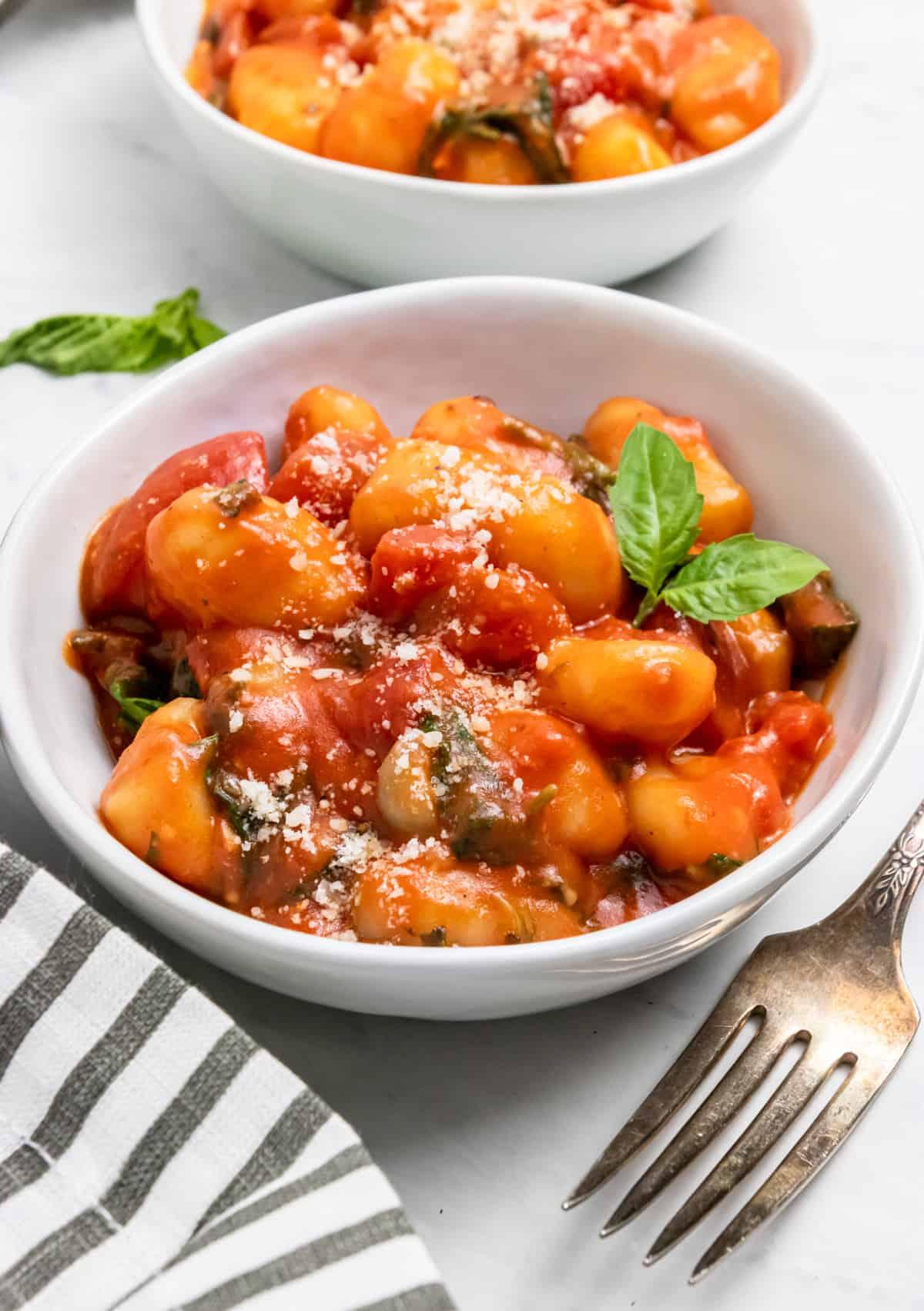 Tomato gnocchi in white bowl with fresh basil.