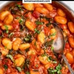 Tomato Basil Gnocchi in pot with fresh basil and spoon.