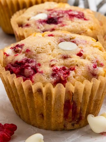 White chocolate raspberry muffins on parchment paper.