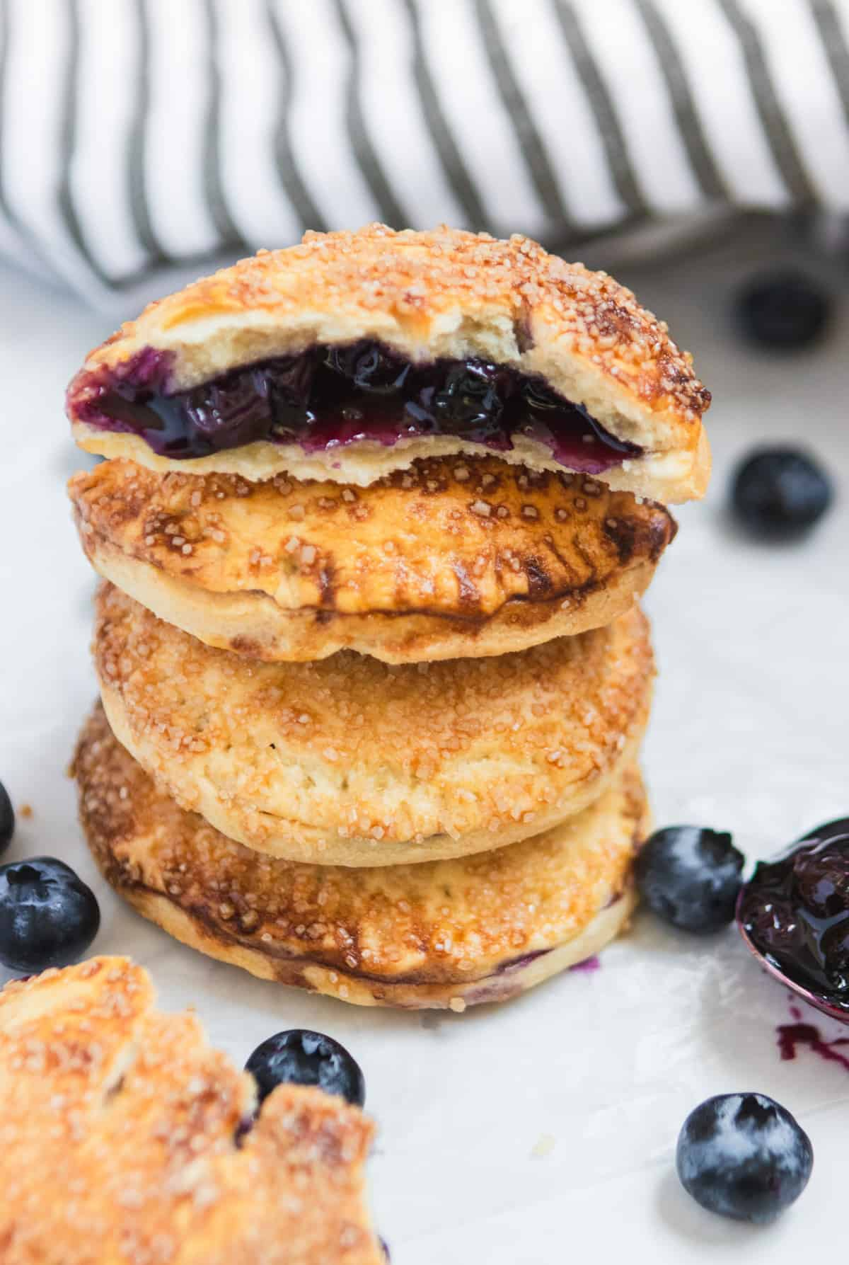 Stack of air fryer hand pies with blueberry filling in top cut pie.