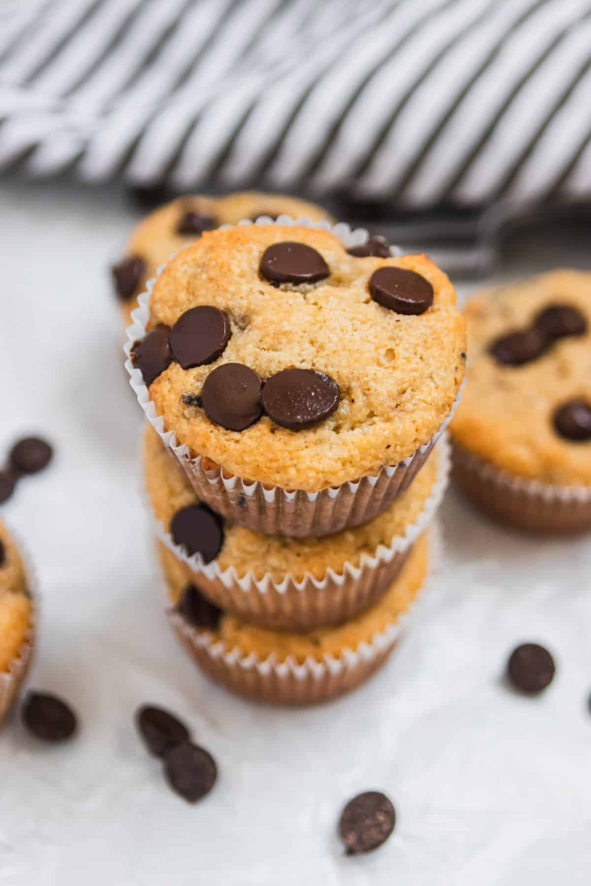 Stack of almond flour banana muffins with chocolate chips on wax paper.