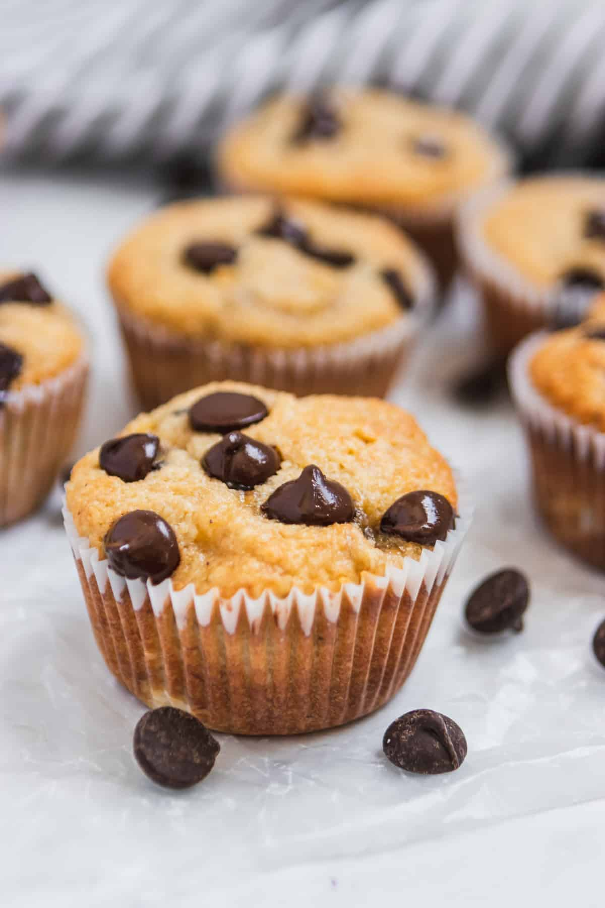 Banana muffins with chocolate chips on wax paper.