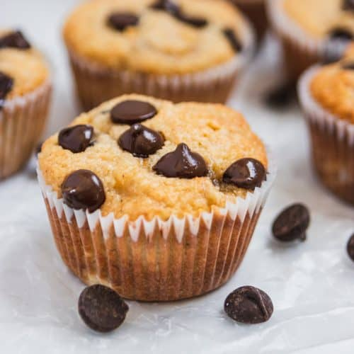 Almond flour banana muffin with chocolate chips on wax paper.