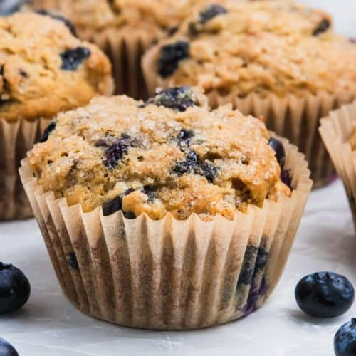 Banana blueberry muffin on counter with blueberries.