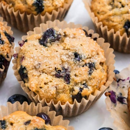 Banana blueberry muffins with blueberries on counter.