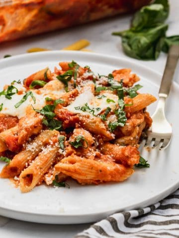 Chicken parmesan casserole on plate with fresh parsley.